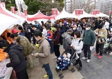 熊本城マラソンの受け付けが始まり、ナンバーカードなどを受け取るランナーの行列ができた辛島公園=15日、熊本市中央区(小野宏明)