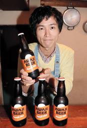お薦めの淡路島の地ビールを手にする石だたみボーイズリーダーの今井万喜さん=東灘区田中町3