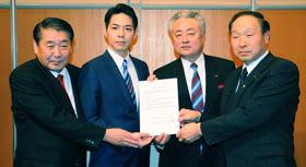 遠藤連副会長(右から2人目)ら自民党道連幹部とともに協定書を手にする鈴木氏(同3人目)