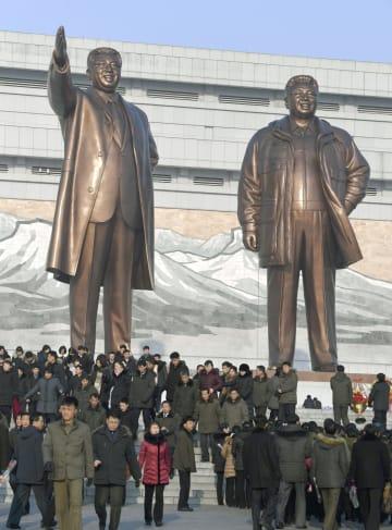 北朝鮮の故金正日総書記の生誕記念日を迎え、故金日成主席(左)と金総書記の銅像が立つ平壌の「万寿台の丘」を訪れた市民ら=16日(共同)