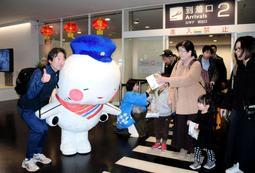 到着客らに記念品を手渡す関西エアポートの社員とキャラクター「そらやん」=16日午前、神戸市中央区神戸空港