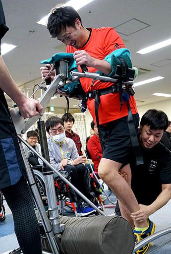 スタッフに支えられながら懸命に一歩を踏み出す参加者=10日、大阪市北区