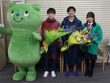 花束を贈られ笑顔を見せる大村・東彼のアンカー横山(近大、右から2人目)と北松・松浦のアンカー中山(第一工大、右から3人目)=松浦市、親和銀行松浦支店
