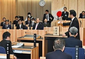 【田岡実千年市長(中央)らが見守る中、記名投票によって補正予算案の採決をする議員=16日午前4時10分ごろ、和歌山県新宮市で】