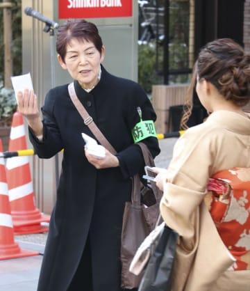 情報提供を求めて、事件概要が書かれたチラシ入りのティッシュを配る後藤博樹さんの母親リウさん=16日午後、東京都府中市の京王線府中駅前