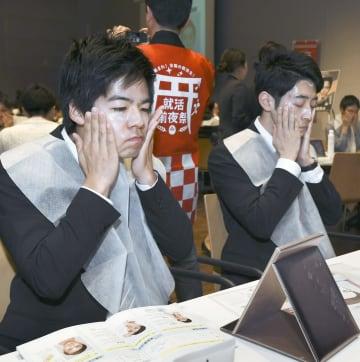 資生堂が開いた美容セミナーで、顔にクリームを塗る男子学生ら=16日午後、東京都内
