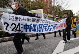 県民投票への関心を呼び掛ける横断幕や看板を手にデモ行進する人たち=16日午後、神戸市中央区加納町6