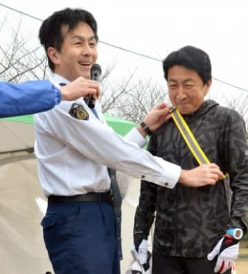 参加者にたすきを掛ける県警交通企画課の奥田和也係長(左)=鹿児島市の吉野公園