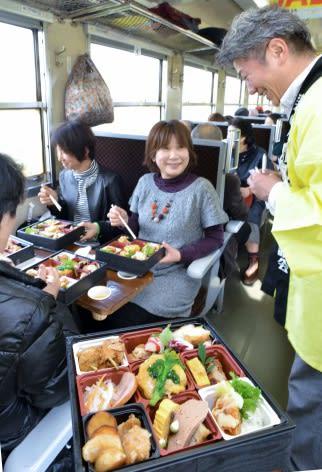 鶏を使った料理を楽しむ参加者=貸切列車「うんまか鶏号」車内