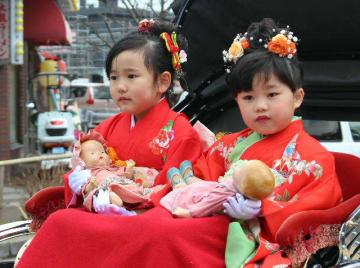 パレードで2体の「青い目の人形」を抱いて人力車に乗る園児