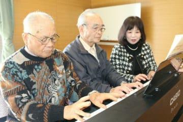 公民館まつりに向けて6手連弾の楽曲の練習をする福田克充さん(左)、江良孝二さん(中央)と講師の衛藤正子さん