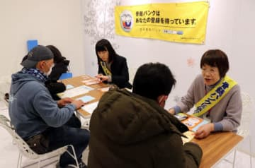 ドナー登録の希望者(手前)に手続き方法を説明する土居代表(奥右)たち