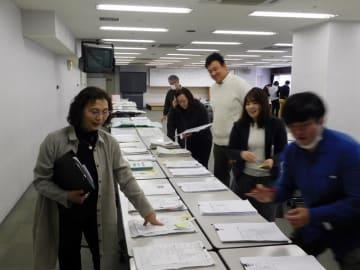 小中学生の手作り新聞を慎重に審査する審査員たち=16日、千葉市中央区の県教育会館