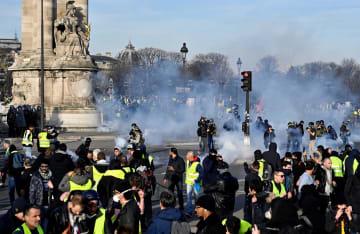 16日、パリで警官隊と衝突する黄色いベスト運動のデモ参加者(ゲッティ=共同)