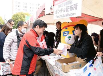 熊本城マラソンの受け付け会場で自ら作った防寒ポンチョをランナーに手渡すHKT48の田中美久さん(右)=熊本市中央区