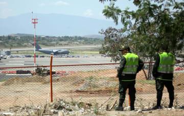 16日、コロンビア北部ククタの空港に到着した支援物資を積んだ米軍機(奥)と地元の警察官(ロイター=共同)