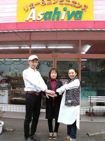 20日に閉店する「リカー&コンビニエンスAsahiya」の前で手を合わす井戸公子さん(中央)と加藤太一さん(左)、恵美さん=七宗町神渕