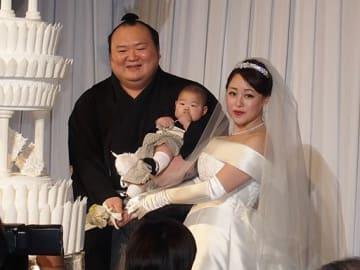 長男を抱いてウエディングケーキに入刀する宝富士関と英莉乃さん