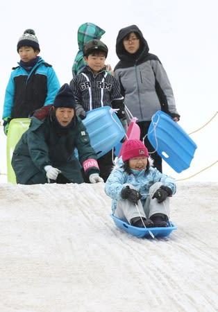 雪の滑り台でそりを楽しむ子どもたち=16日、長岡市千秋3