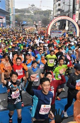 熊本城をバックに、フルマラソンの部でスタートするランナーたち=17日午前9時2分、熊本市中央区のびぷれす熊日会館前(池田祐介)