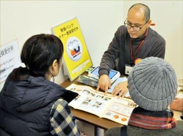 骨髄バンクについて池田さんから説明を受ける新規ドナー登録者(手前の2人)=徳島市の献血ルームアミコ