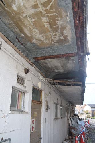 1階廊下の屋根が剥がれ落ち、鉄骨周りのアスベストを含む吹き付け材がむき出しになっている