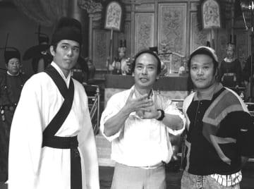 映画「敦煌」の宮廷セット前で、佐藤浩市さん(左)と西田敏行さん(右)に撮影イメージを説明する佐藤純弥監督=1987年5月、北京(共同)