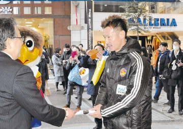 仙台市内の商店街を回り、商店主らにクラブのポスターを手渡す菅井さん(右)
