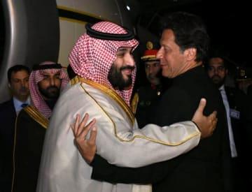 パキスタン首都近郊の空軍基地で、サウジアラビアのムハンマド皇太子(左)を出迎えるカーン首相=17日(パキスタン政府提供、ロイター=共同)
