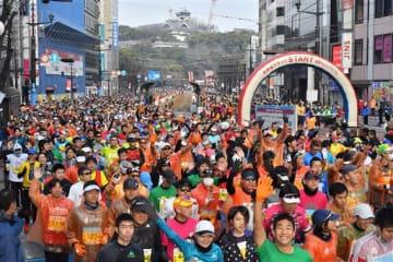 熊本城をバックにスタートするフルマラソンのランナーたち=17日午前9時5分ごろ、熊本市中央区(池田祐介)