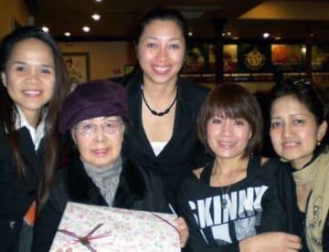 フィリピン出身の女性らに囲まれる小川さん(左から2人目)=2012年2月、湯沢市