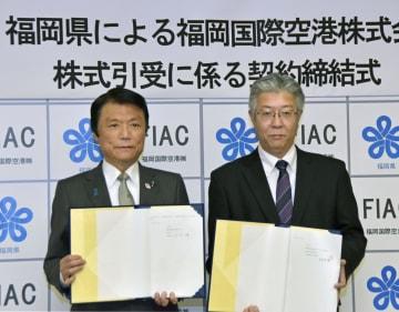 「福岡国際空港」と株式取得の契約を締結し、写真に納まる福岡県の小川洋知事(左)と同社の永竿哲哉社長=18日午前、福岡県庁