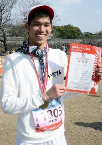 熊本と愛媛の復興を願って2週連続でフルマラソンを完走し、笑顔を見せる山本奎祐さん=17日、熊本市中央区
