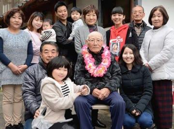 津川藤雄さん(前列中央)の家族と写真に納まるケイレン・クラミツさん(同右)=美里町