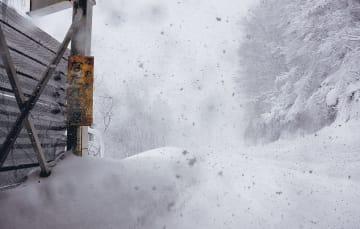 雪が降りしきる大覚野峠区間。着雪した看板には「この先なだれ注意」と書かれていた=2月上旬、北秋田市阿仁