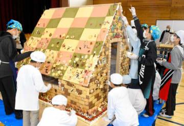 ケーキのスポンジなどで作られたお菓子の家をクッキーやチョコレートなどで飾り付ける子どもたち