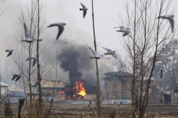 18日、インド北部ジャム・カシミール州で、銃撃戦の最中に武装勢力が避難したとみられる住宅。炎や煙が立ち上っている(AP=共同)