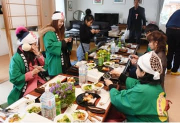 日本の正月料理をスマートフォンなどで撮影するタイのツアー参加者ら=鹿屋市上高隈の癒しの宿もみじ