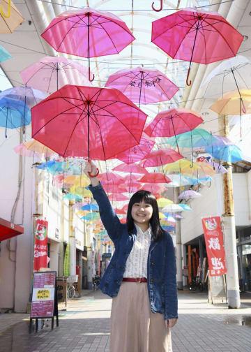 宮崎県日南市の油津商店街につるされた色とりどりのビニール傘と企画した穐田南海さん=16日