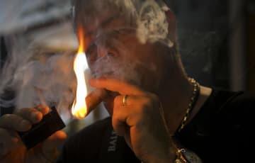 18日、キューバ・ハバナで行われた国際葉巻フェスティバルで、葉巻に火を付ける男性(AP=共同)