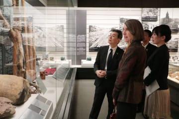 原爆被害を伝える資料や写真を見つめるケリー理事長(左から2人目)=長崎市平野町、長崎原爆資料館