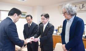 善意を届けた市民たちを代表し、目録を手渡す亀谷理事長(中央)