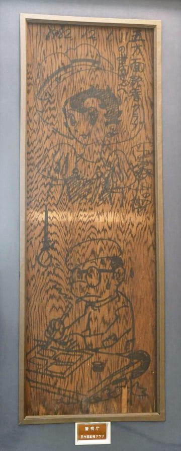 トキワ荘解体時に取り外され、手塚治虫さんが若手記者に贈った天井板。「リボンの騎士」のキャラクターと、自身の姿が描かれている