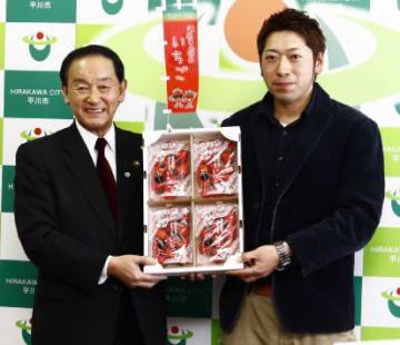 よつぼしを手に平川市での生産拡大を期待する松田さん(右)と長尾市長