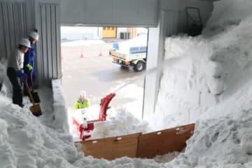 ワインの熟成に活用する雪を雪室に搬入する作業=15日、上越市