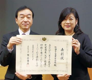 表彰状を掲げる仙北屋校長(左)と学習支援ボランティアコーディネーターの関根美咲さん