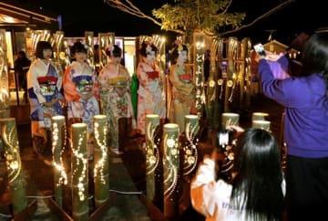 竹灯籠が並ぶ「ひとよしまち燈り」の会場で記念撮影する観客ら=人吉市