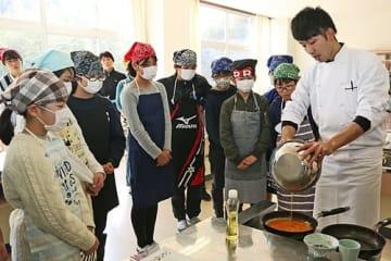 【更井亮介さん(右)から、ジビエを使った料理を教わる児童=18日、和歌山県田辺市上芳養で】