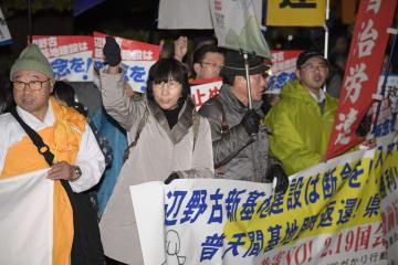 米軍普天間飛行場の沖縄県名護市辺野古移設に反対し、国会前でデモ行進する参加者=19日夜