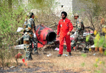 19日、インド南部ベンガルールの空軍基地近くで、墜落機の残骸近くに立つ兵士ら(ロイター=共同)